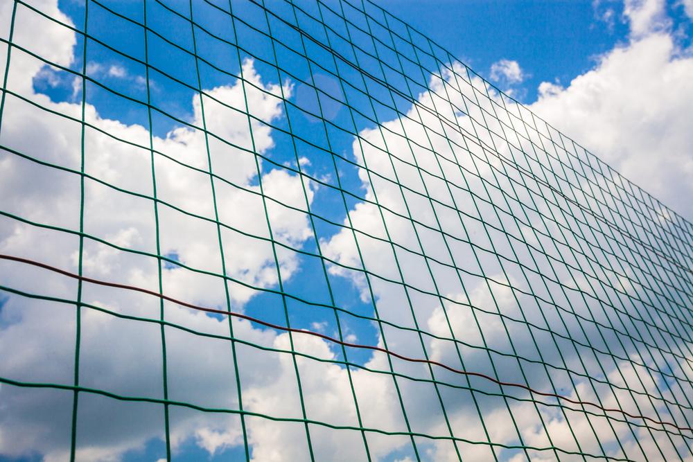 Humannet By Shutterstock, a cloudy sky is seen through a net