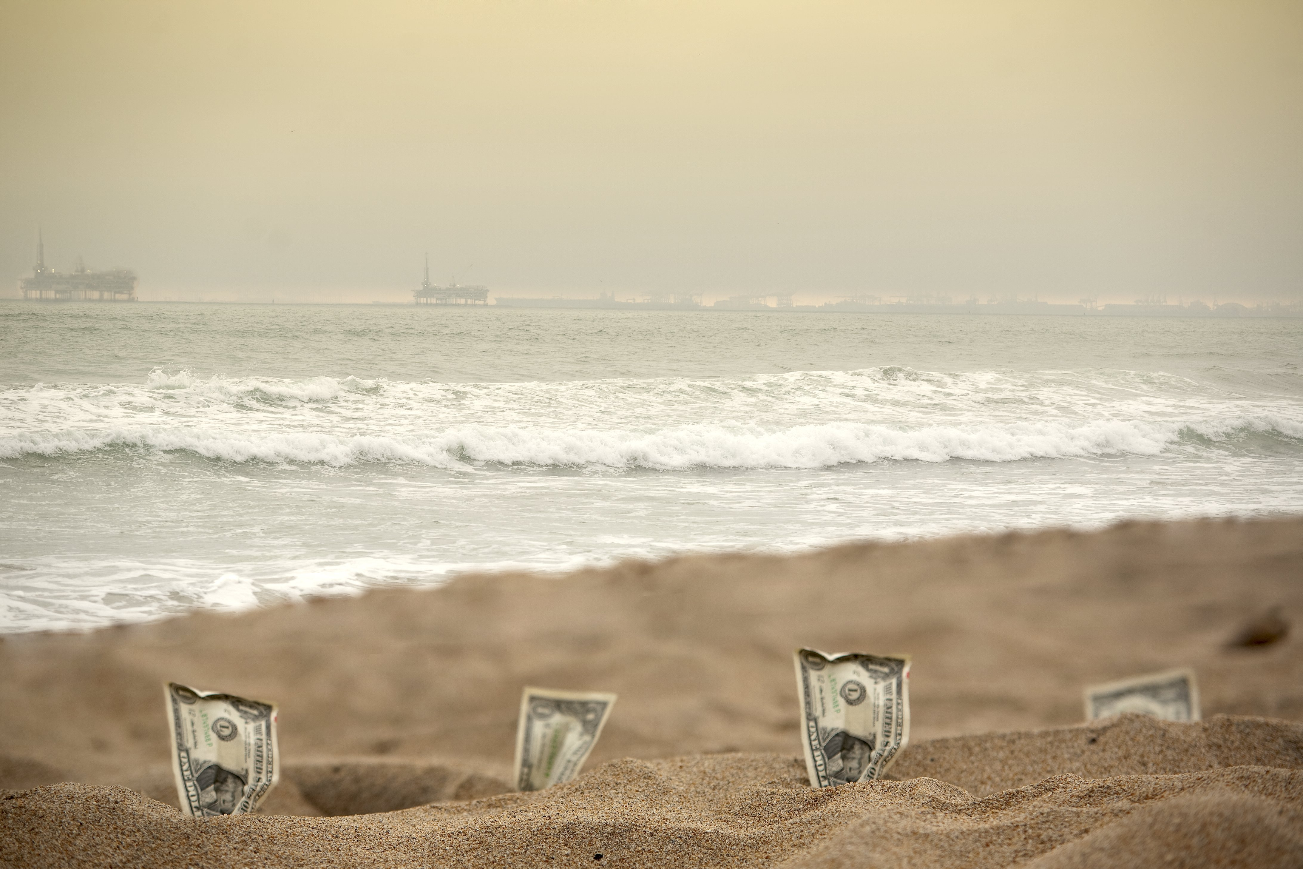 Zen Photo-graphic by Shutterstock, four dollar bills standing in thesand in the beach and waves hitting the shore