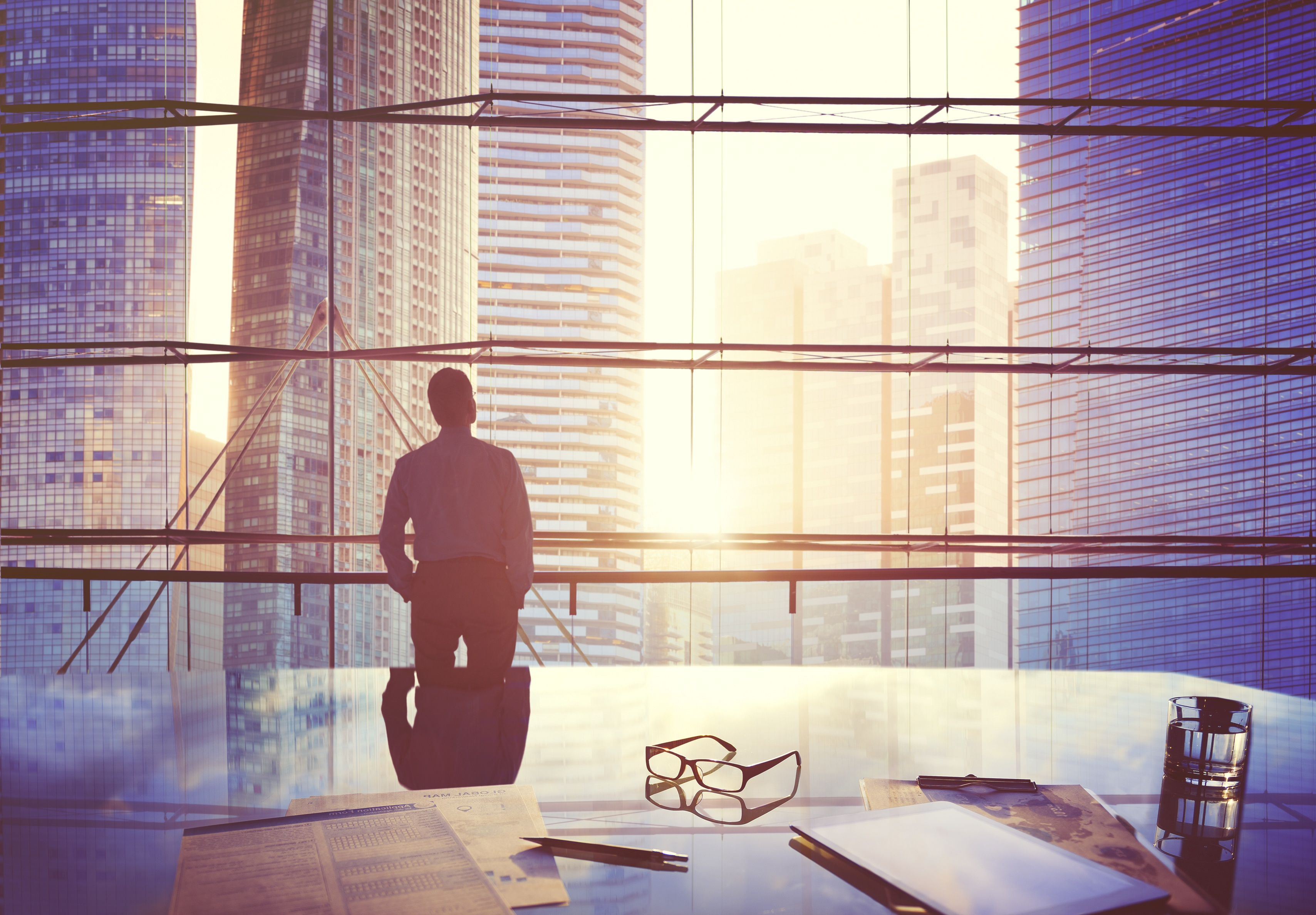 Rawpixel.com by Shutterstock a man in a suit standing in front of a big window and watching sunset between skyscrapers