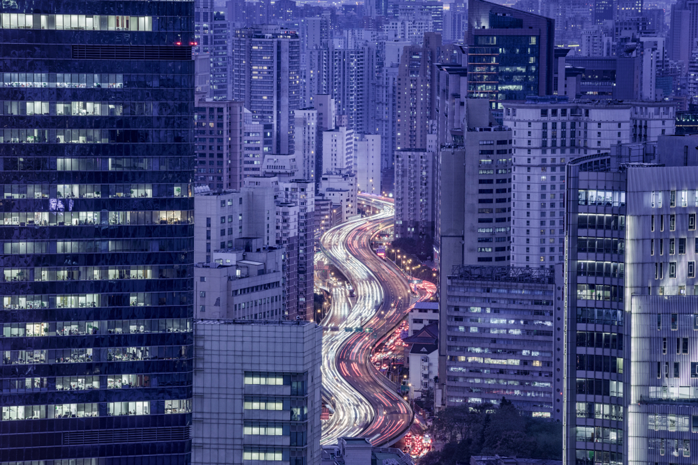 Yibo Wang by Shutterstock, a picutre of city buildings and a road going between buildings