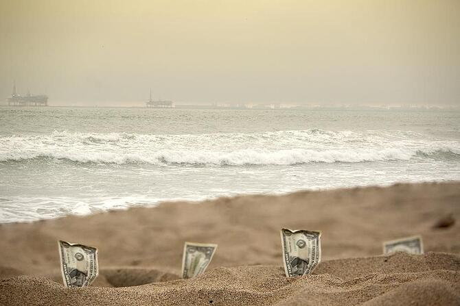 Zen Photo-graphic by Shutterstock.jpg Idel cash, dollar bills laying on the beach