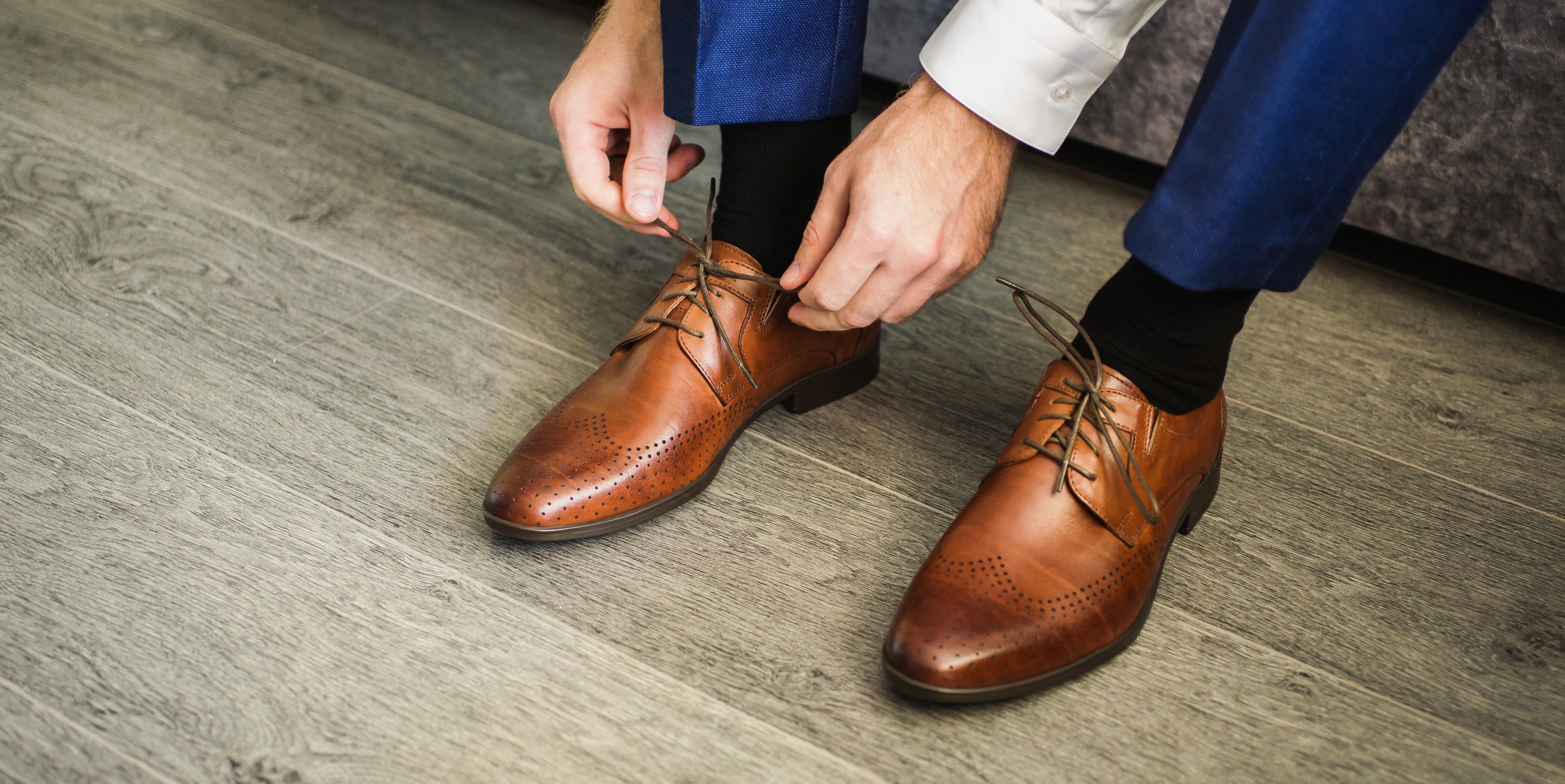 iiiphevgeniy by Shutterstock, a man in a suit ties shoelaces of brown shoes